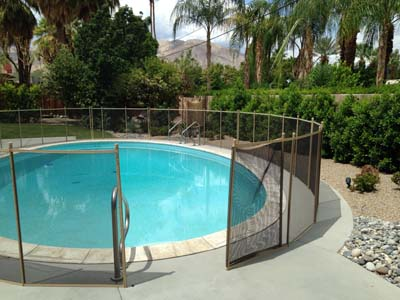 Fold back pool fence opening on sand and brown fence in Palm desert